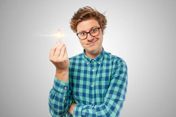 A nerd looking at camera with a light bulb in his hand and he's just had an amazing idea for something