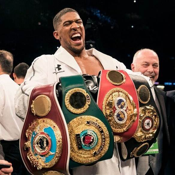 Joshua holding his 4 heavyweight belts